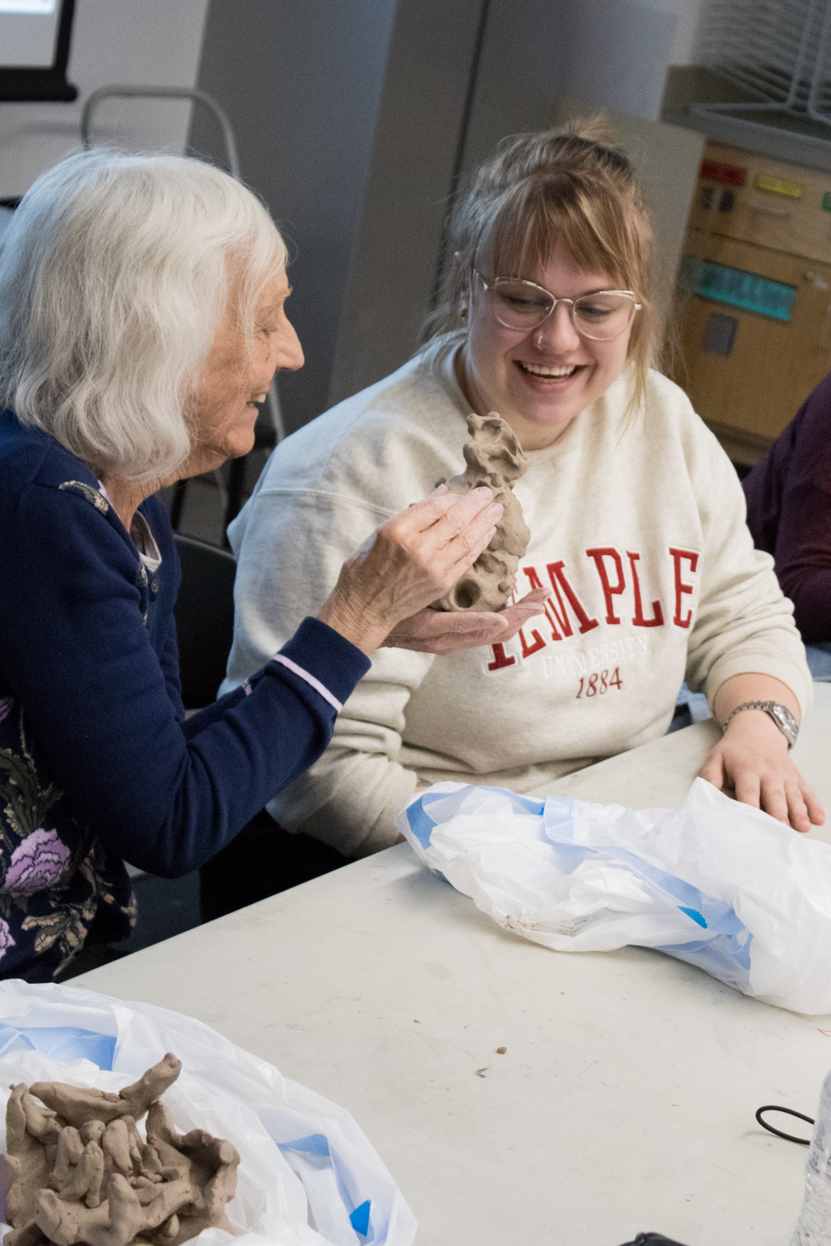 Carol Saylor uses her hands to examine a student's clay sculpture.