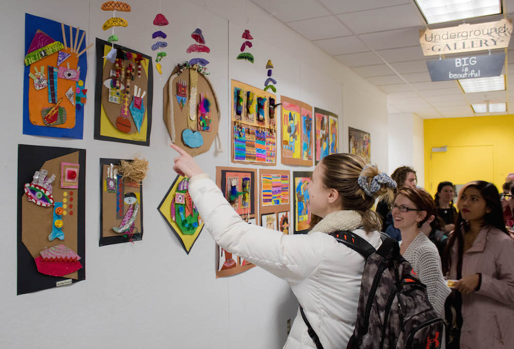 Art Education students admire the the student work.