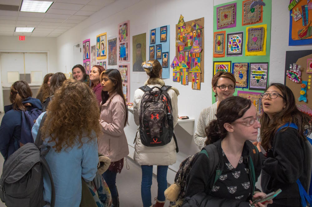 Art Education students gather to view the work.
