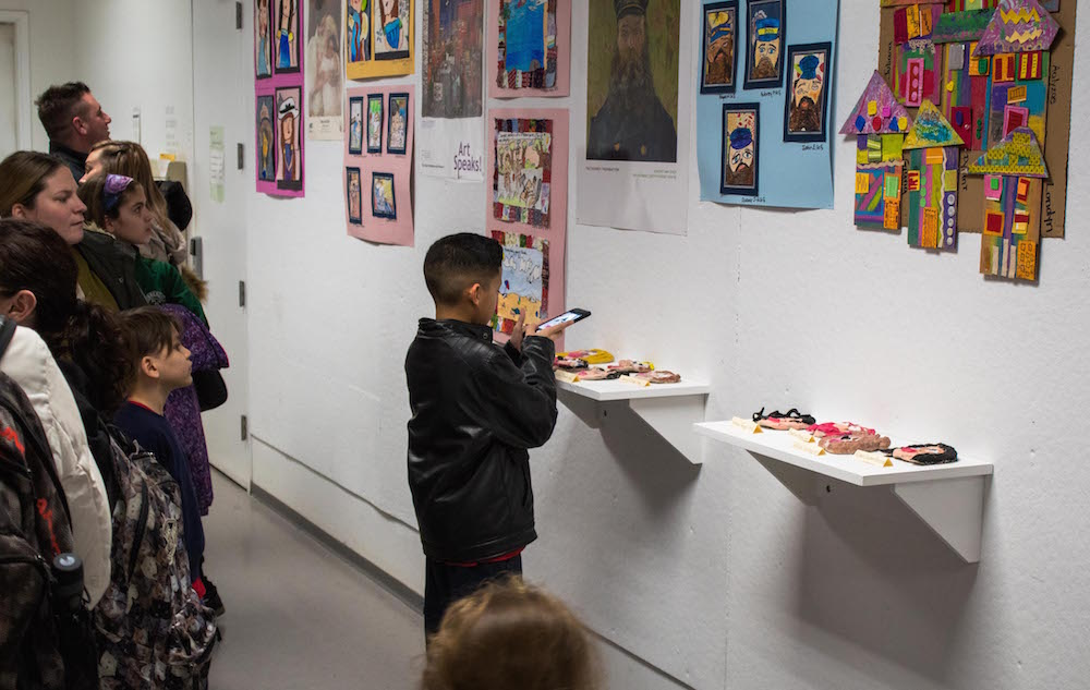 Parents and students view and photograph their work