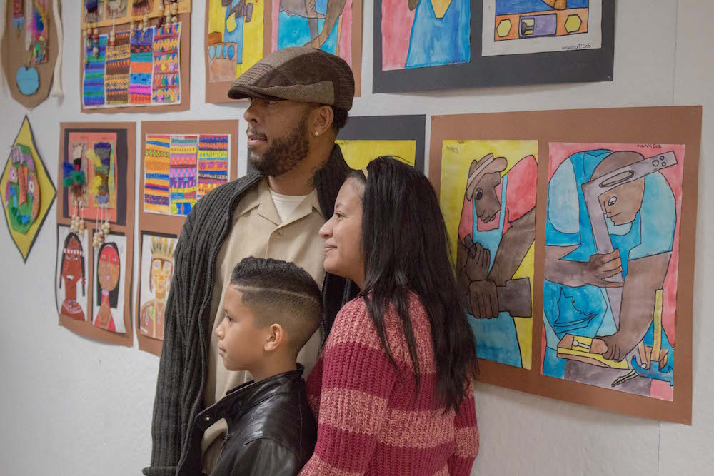 A family poses in front of a student's artwork.