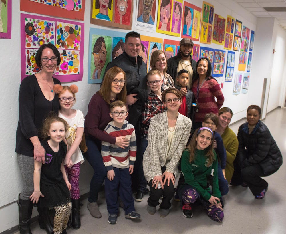 Students, their families, and Ms. Potlocki pose in front of artwork.