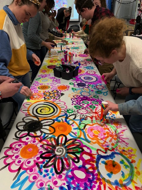 Student teachers participate in a collaborative art piece during the workshop.