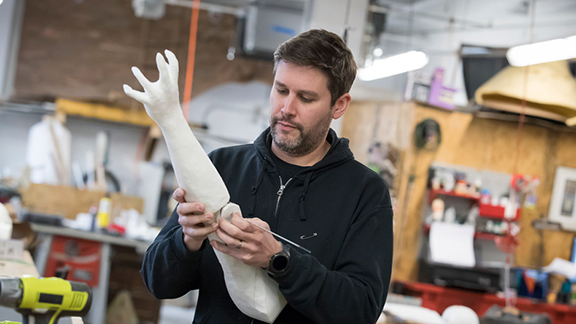 Michael Latini works on a piece of the puppet he and his team are building for Charlie and the Chocolate Factory on Broadway.