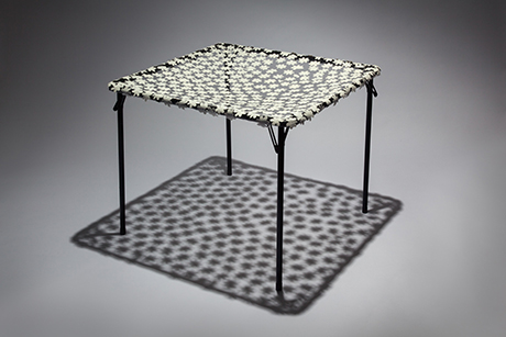 Card table with a sheer floral top.