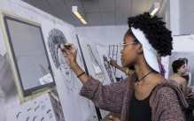 A student drawing a self-portrait