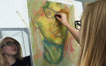 Photo of a student drawing a colorful pastel self-portrait while looking in a mirror.
