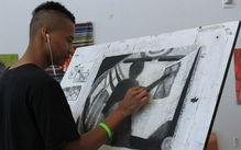 Students working on a charcoal drawing on a drawing desk.