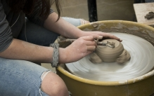 Student working on the ceramics throwing wheel