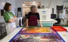 View in Tyler's Fibers studio of instructor and student discussing student's color textile pieces.