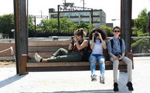 Three students are sitting on city park bench taking photos with digital cameras