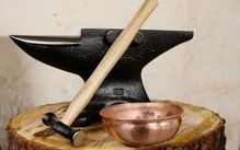 Photo of an anvil, hammer, and hammered copper bowl on a tree trunk.