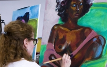Adult student painting a bright figure painting of a female figure model.