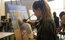 student works on painting in classroom