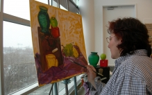 Adult female student painting a still-life in oils.