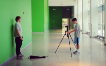 Two students filming video with a tripod in a long green hallway.