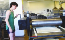 Printmaking student rolling their design out