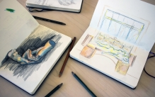 Collection of open sketchbooks showing pencil drawings.