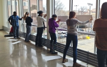 Students drawing up against large windows