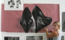Photo of student working on a charcoal drawing of a pair of high heels