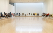 line of different chairs hung around the perimeter of empty exhibition space