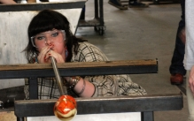 Female student blowing molten glass at the end of a metal glass blowing pipe.