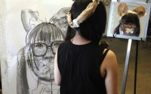 Student wearing paper cat ears and looking into a mirror while drawing a large charcoal self-portrait.