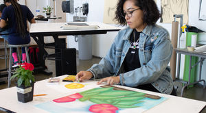 Student in a drawing studio working on a colorful pastel drawing of a flower.