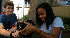 Female student using a digital camera outdoors with a male student.