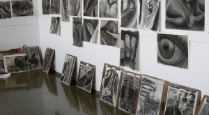 Wall of hanging black and white charcoal drawings by students.