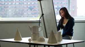 Female student at an easel drawing a still-life of several objects