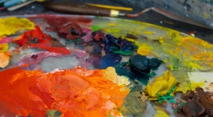 Photo of brightly colored oil paint smears on a painting palette.