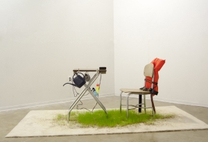 Installation with carpet, grass, lightbox table, chair, lamp, watering can, life preserver, fishing bobber