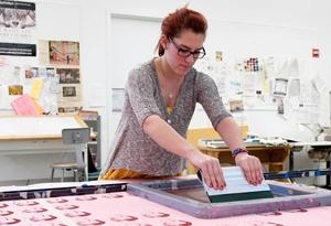 female student screen printing on fabric