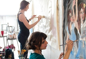 two girls painting on paper pinned to wall