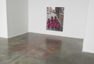 Red tape in Chinatown sidewalk pattern on the floor with a large digital photo print of a little Chinese girl repeated.