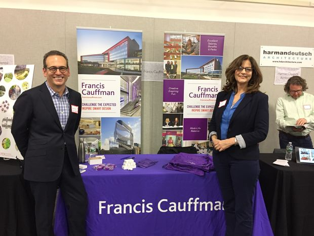 Two representatives from FCA Architects stand in front of their Career Fair booth.