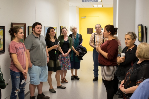 Art Educator Jamie Forslund gives talk to attendees at reception for Ver de lejos Exhibition
