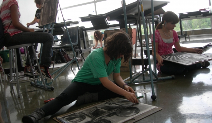 A few drawing students sitting on the ground and working on their pieces in the studio