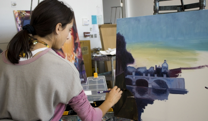 Student painting a peaceful landscape