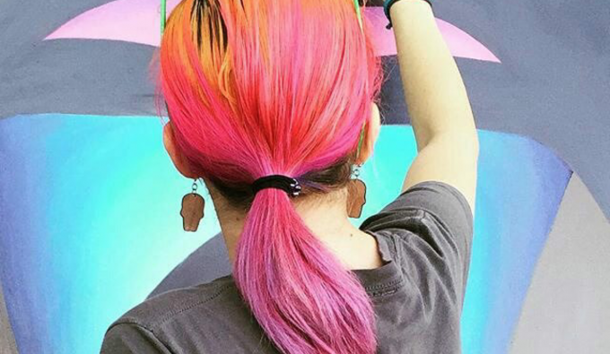 Student with colorful hair in front of a colorful oil painting
