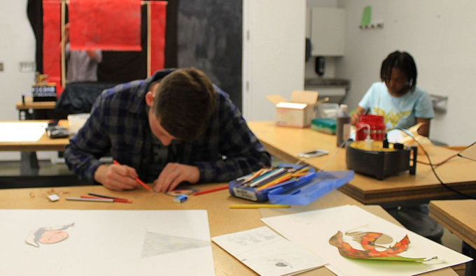 Two visual studies students work in their studio classroom on projects
