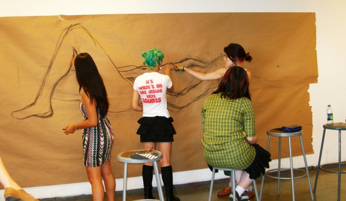 Students sketching a large figure together on really big paper hung on the wall.