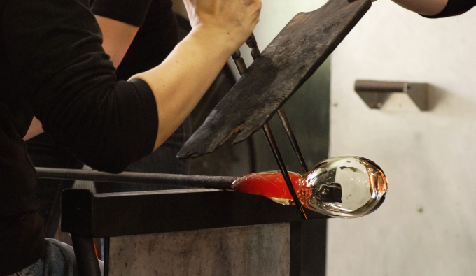 Close up shot of student working on a blown glass form