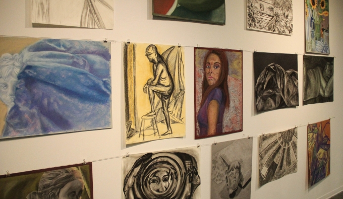 View of a group of pastel and charcoal drawings on a gallery wall