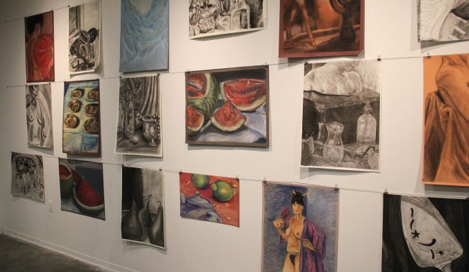 View of a group of charcoal and pastel drawings on the gallery wall