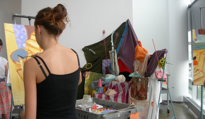 Student painting a colorful still life.