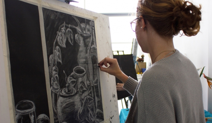 Student drawing a still life on black paper with white conte