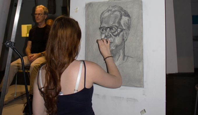 Student using black and white charcoal on grey paper to draw an older man's head with glasses.