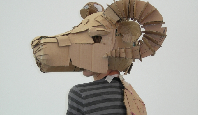 Student wearing hand made cardboard mask of a ram's head.